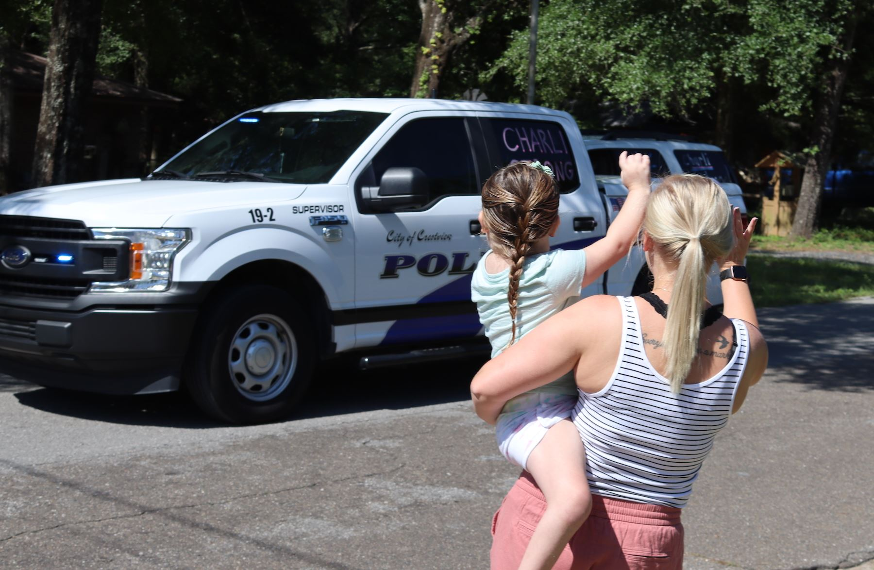 Charli Betts, 5, and her mother, Bree, wave to a passing Crestview Police pick-up which was part of
