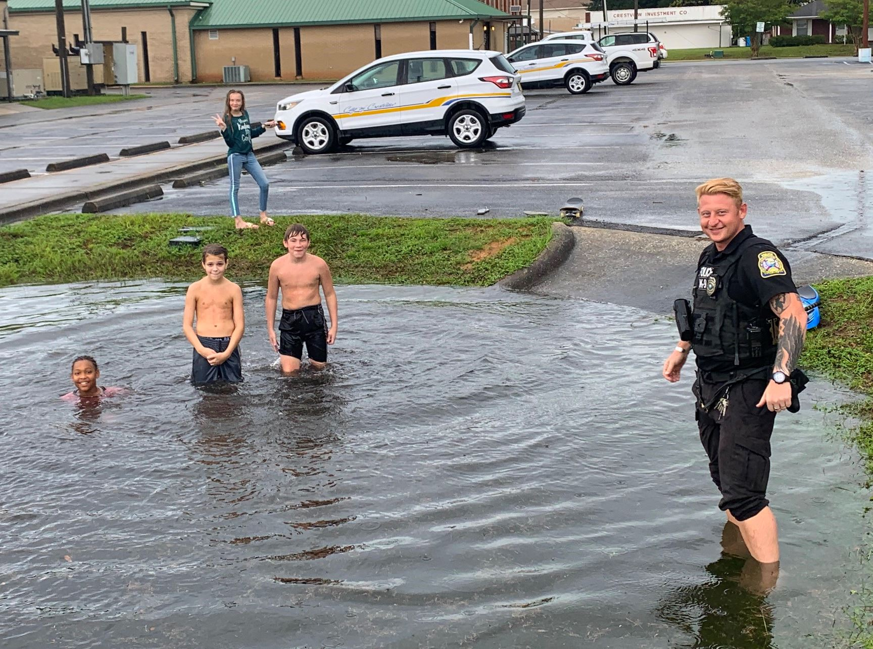 Crestview Police K9 Officer Nate Marlar joins some kids frolicking in a City Hall retention pond.