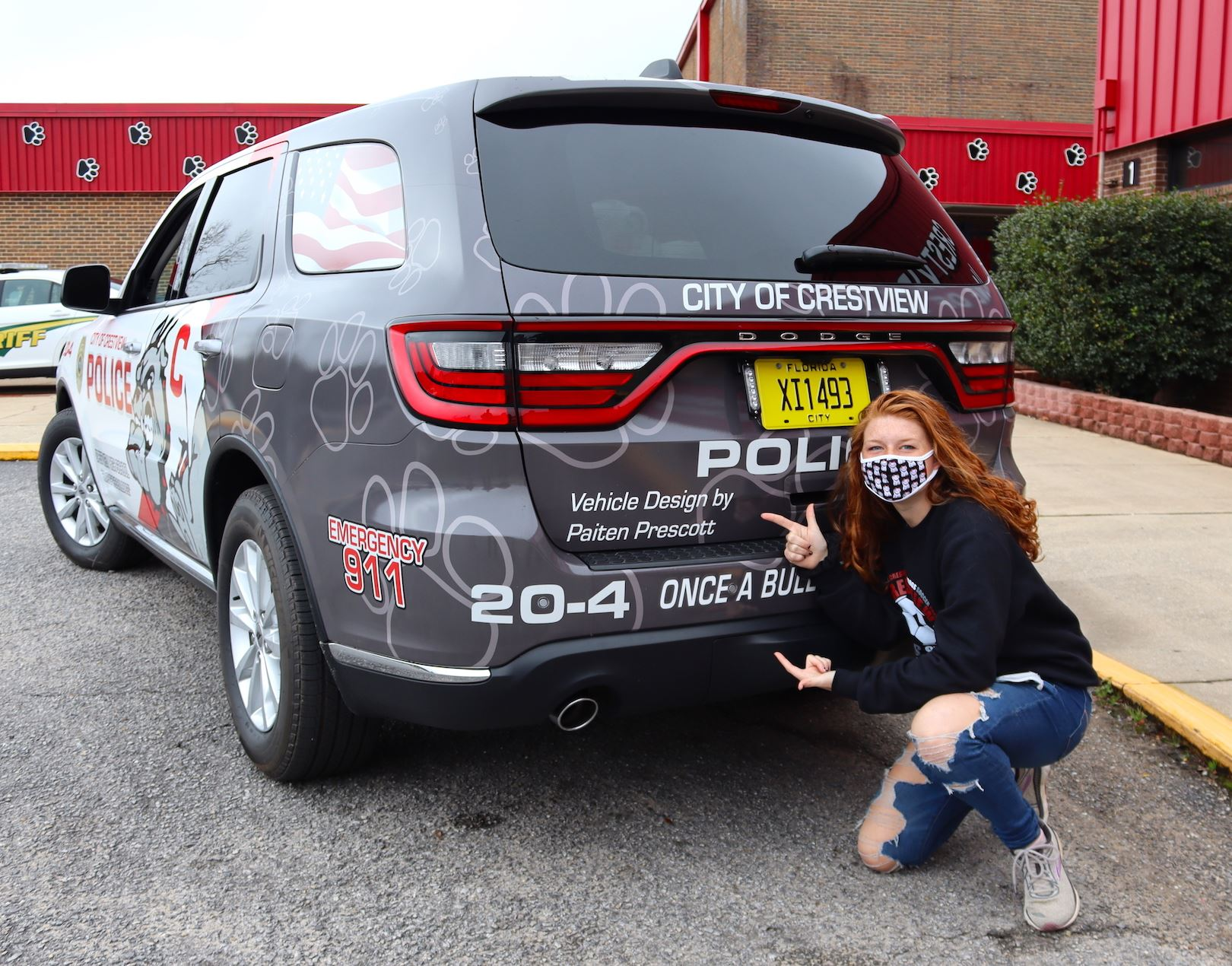 A Crestview High School student poses next to the police car for which she designed graphics