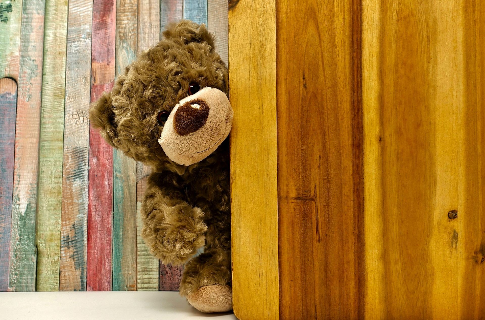 A stuffed teddy bear peeks out from behind a wall.